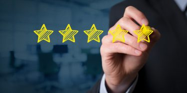 Review, increase rating, performance and classification concept. Businessman draw five yellow stars to increase rating of his company, office in background.
