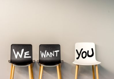 Job recruiting advertisement represented by 'WE WANT YOU' texts on the chairs. One chair is colored differently and labeled 'YOU' to represent the hiring position to be recruited and filled.