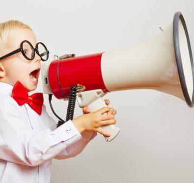 Kind mit brille ruft laut in ein großes Megafon