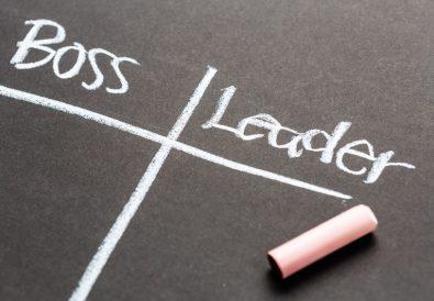 Boss versus Leader concept on chalkboard