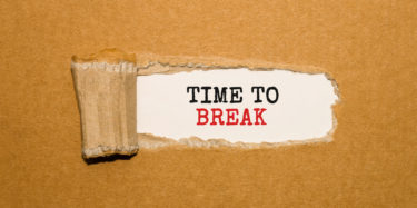 The text TIME TO BREAK appearing behind torn brown paper